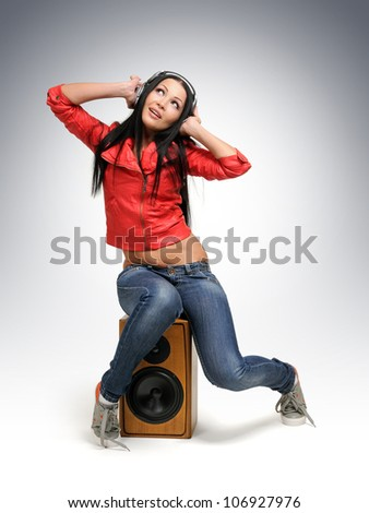 Young beautiful girl in headphones with wooden speaker, sound concept - stock photo