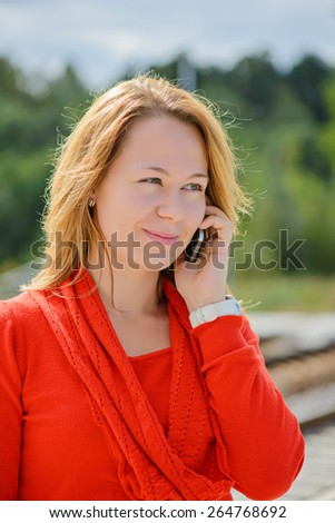 Young beautiful girl in red talking on mobile phone. Shallow depth of field. Focus on the left eye - stock photo