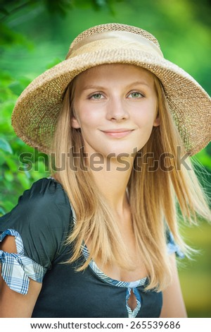 Young beautiful girl in straw hat against city park. - stock photo