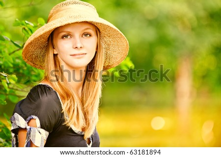 Young beautiful girl in straw hat against lake in city park. - stock photo