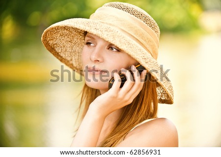 Young beautiful girl in straw hat against lake in city park speaks by mobile phone. - stock photo