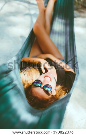 young beautiful girl in sunglasses denim shorts and shirt posing while lying on a hammock, beautiful woman, brunette resting on vacation at the beach, relax, outdoor portrait - stock photo