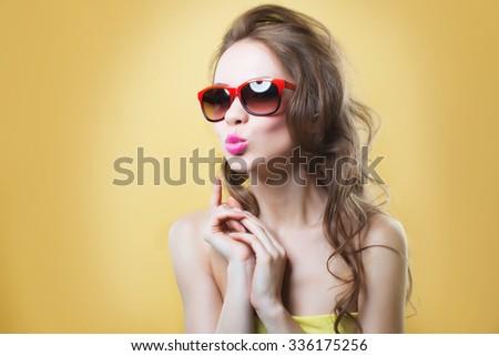 Young beautiful girl in sunglasses on a gold background