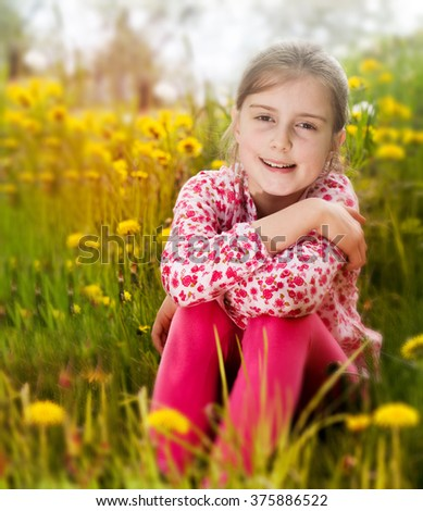 young beautiful girl in the field of dandelions - stock photo