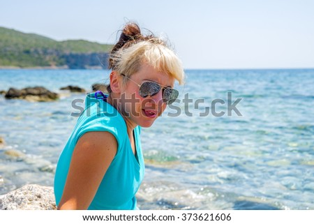 Young beautiful girl in trendy hairstyle playing by the sea in a beautiful beach in Santorini, Greece.