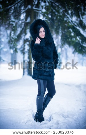 Young beautiful girl in winter clothing,smiling, and walking through the snow - stock photo
