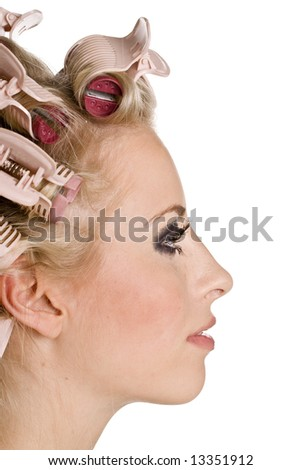 Young beautiful girl is having hair curlers on her head - stock photo