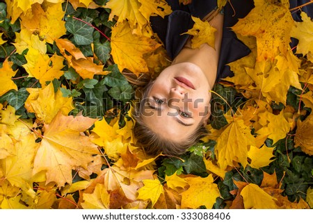 Young beautiful girl lies on a yellow autumn fallen leaves. Close-up portrait, top view. - stock photo