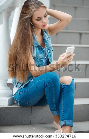 Young beautiful girl listening to MP3 player in the street. Funny teen girl singing and listening music from a smart phone with headphones. teen girl portrait outdoor witting on stairs - stock photo