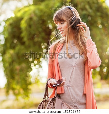 Young beautiful girl listening to MP3 player on the street - stock photo