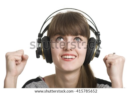 Young beautiful girl  listening to music on here headphones. Over white background