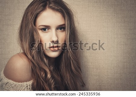 Young beautiful girl looking at camera, dramatic look, art portrait  - stock photo
