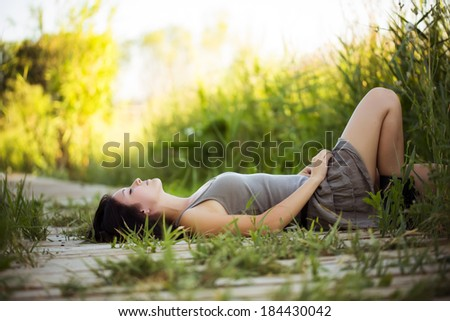Young beautiful girl lying in nature. - stock photo