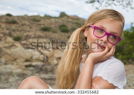 Young beautiful girl model long curly blond hair smiling in pink glasses and a chic dress at the pool with railing and rocks and the sea in Spain, Greece, Santorini - stock photo