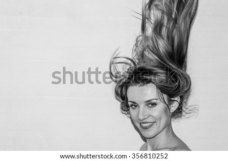 Young beautiful girl model posing smiling with positive emotions with her long hair on a light background black and white photo