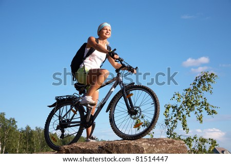 Young beautiful girl on a mountain bike and the blue sky in the park - stock photo