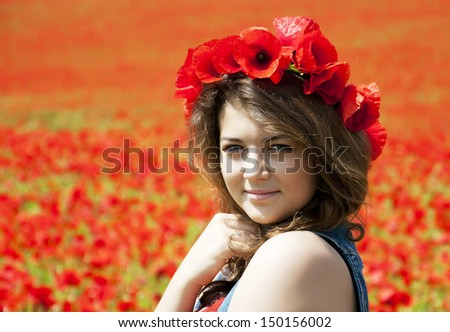 Young beautiful girl  on the poppy flowers