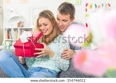 Young beautiful girl opening a present form her boyfriend - stock photo