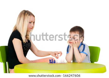 young beautiful girl playing chess with the handsome little boy - stock photo