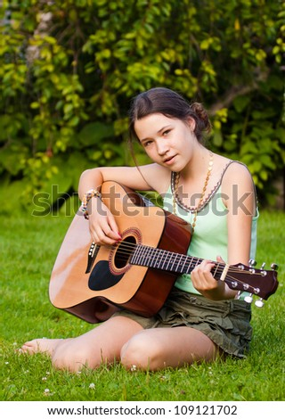 Young beautiful girl playing the guitar and singing in the park - stock photo