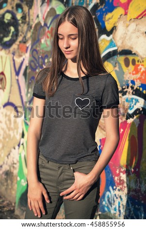 Young beautiful girl posing on a sunny day near the wall with graffiti