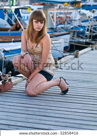 young beautiful girl posing on the pier - stock photo