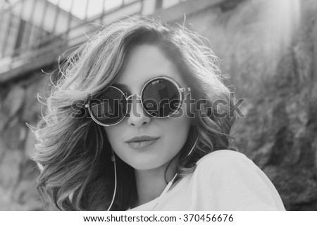young beautiful girl posing on the street, listening to music through earphones, posing on the street, emotional portrait, beautiful blue eyes, a cute face, model looks outdoor portrait black in white - stock photo
