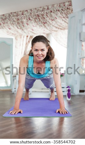 Young beautiful girl practicing fitness at home. Pushups. yoga studio in the daytime. Purple yoga mat.