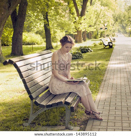 young beautiful girl reading in sunny park - stock photo
