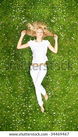 Young beautiful girl reading laying on the grass