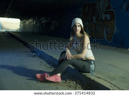 Young beautiful girl resting after exercise at night on the street