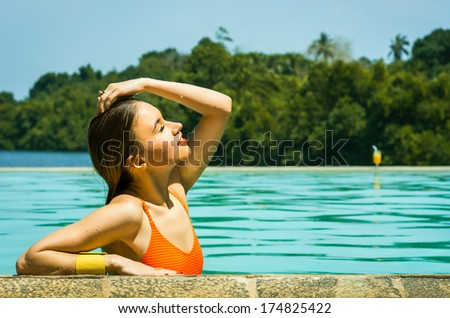 Young beautiful girl resting in the swimming pool