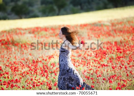 Young beautiful girl running on poppies field. - stock photo