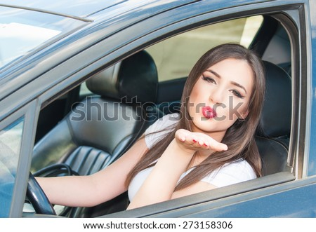 Young beautiful girl send kisses from car - stock photo