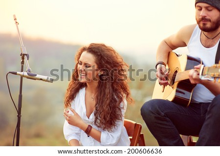 Young beautiful girl singing with a guitar player. - stock photo
