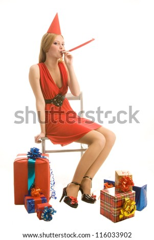 Young beautiful girl sits and blows  on a horn blower, isolated on  white background - stock photo
