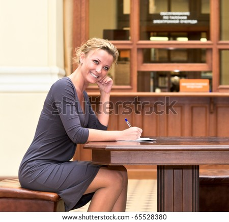 Young beautiful girl sitting at the table, fills out a form and smiling - stock photo