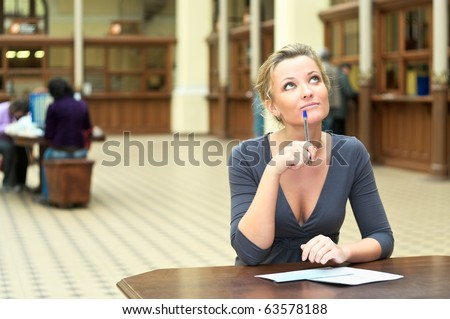 Young beautiful girl sitting at the table thinks. Pen in hand. Copy space