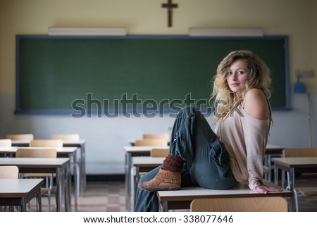 Young beautiful girl sitting on a table in an empty classroom