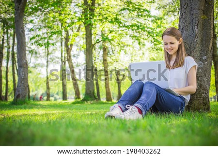Young, beautiful girl sitting on the grass, outdoor, near the tree, with a laptop, smiling, working