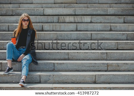 Young beautiful girl sitting on the steps with coffee in glasses. - stock photo