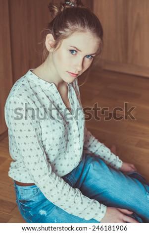 Young beautiful girl sitting on wooden floor, studio portrait  - stock photo