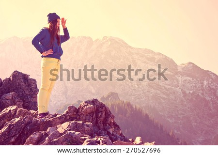 Young beautiful girl standing on the rocks in mountains and looking for new opportunities. Vintage instagram picture. - stock photo