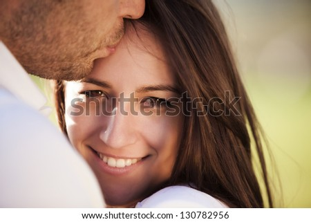 Young beautiful girl staring at camera while being kissed - stock photo