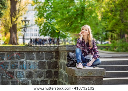 Young beautiful girl student sitting on the steps under the campus, university, school, education preparing to passing exam read the synopsis of the book in notebook thoughtful, interest, intelligence - stock photo