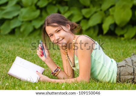 Young beautiful girl studying in the park, lying on grass - stock photo