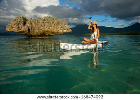young beautiful girl-surfer riding on the stand-up paddle board in the clear waters of the Indian Ocean  of Mauritius island on the background of mountains - stock photo