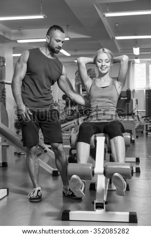 Young beautiful girl takes exercises with a trainer. Training in the gym. Proper exercise. Photos for sporting magazines and websites. - stock photo