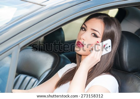 Young beautiful girl talking on the phone while driving - stock photo