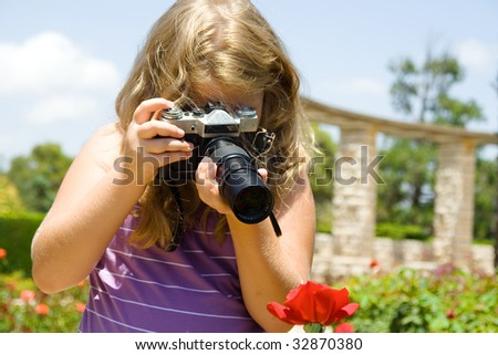 Young  beautiful girl the blonde photographs roses with SLR camera. - stock photo